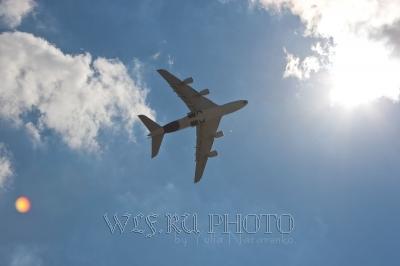 фото самолета в небе на фоне солнца и облаков