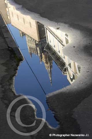 отражение московской высотки в луже после дождя