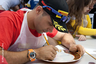 Гонщик Владимир Леонов расписывает тарелку в жостовском стиле